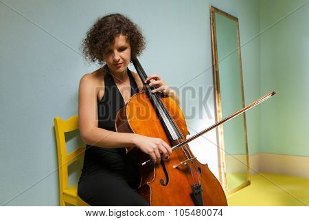 young girl playing cello in a room