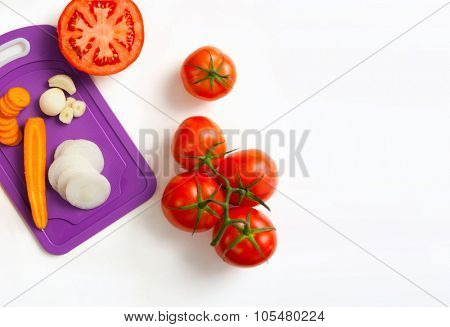 image of fresh tomatoes carrot onion and garlic , whole and sliced, on white background