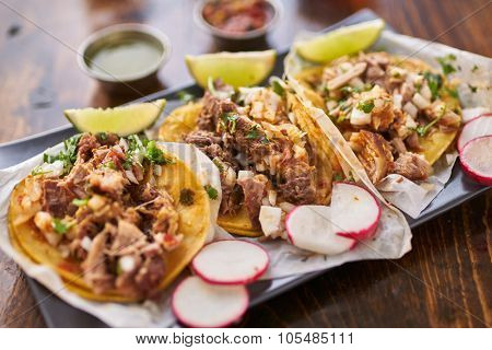 three street tacos in yellow corn tortilla with different meats