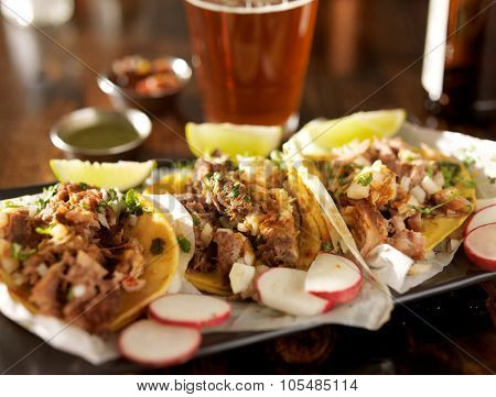 beer and mexican street tacos with radishes shot with selective focus