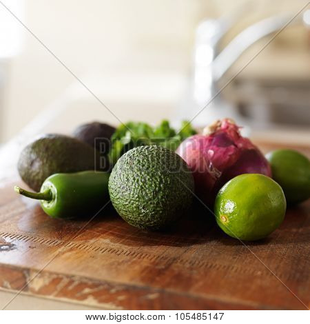 everything needed for guacamole recipe laid out on wooden cutting board
