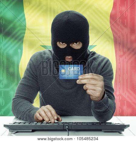 Dark-skinned Hacker With Flag On Background Holding Credit Card - Senegal