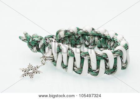 green braided bracelet on white background. snowflake