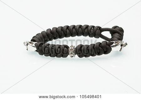 Black braided bracelet with skulls on white background