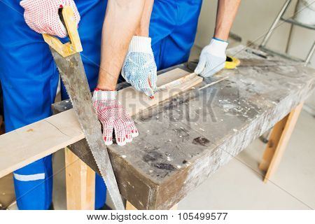 building, carpentry, repair, teamwork and people concept - close up of builders with arm saw sawing board on table