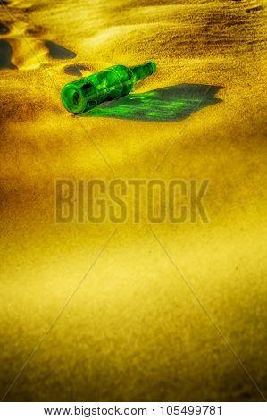 Empty Green Bottle Lying On The Sand