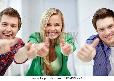 education, people, friendship and learning concept - group of happy high school students or classmates showing thumbs up
