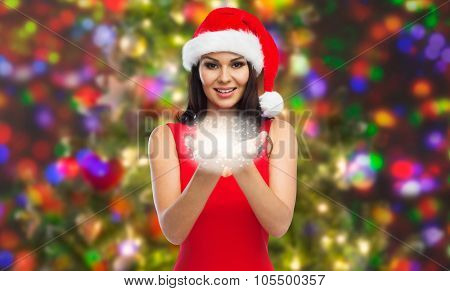 people, holidays, christmas and magic concept - beautiful sexy woman in santa hat and red dress showing fairy dust on palms over party lights background
