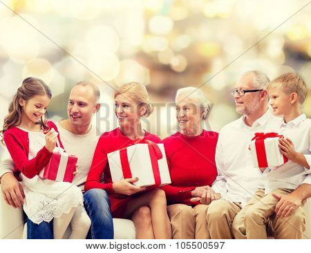 family, holidays, generation, christmas and people concept - smiling family with gift boxes sitting on couch over lights background