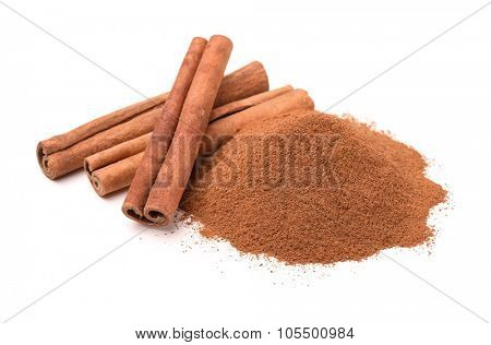 Ground cinnamon and cinnamon sticks isolated on white
