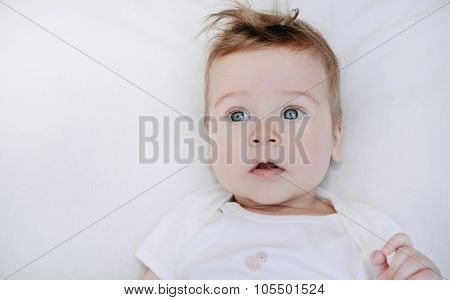 Portrait Of Cute Little Baby Boy Lying On Soft White Pillow