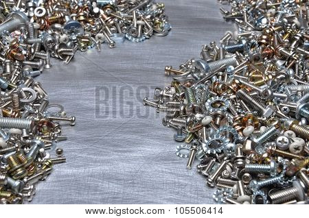 Screws, nuts and bolts on metal background