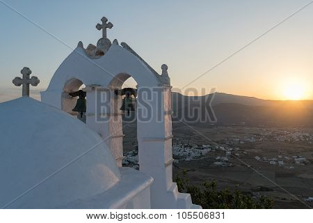 Traditional Greek beauty with a church against the sun on top of a mountain.