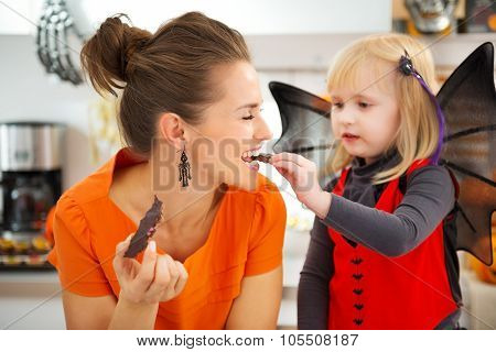 Girl In Bat Costume With Mother Eating Halloween Biscuits