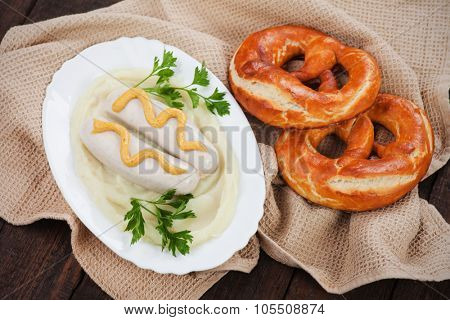 German white sausage or wurst served with mashed potato and pretzel