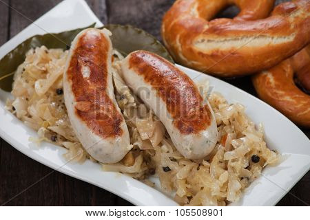 German white sausage or wurst served with sauerkraut and pretzel