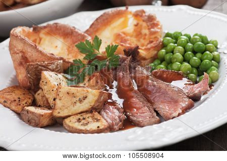 Traditional british sunday roast with yorkshire pudding and vegetables