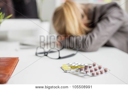 Woman sleeping on desk after taking pills