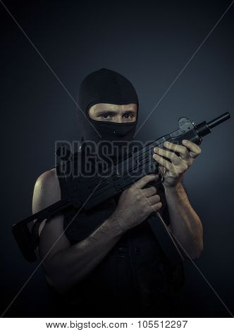 Weapon, terrorist carrying a machine gun and balaclava