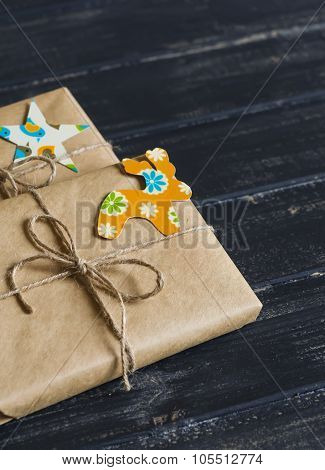 Homemade Gifts In Kraft Paper With Vintage Paper Tags On Dark Wooden Surface