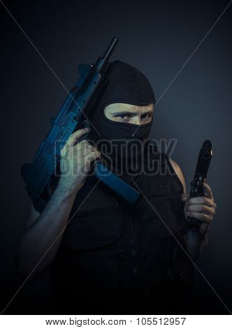 Assassin, terrorist carrying a machine gun and balaclava