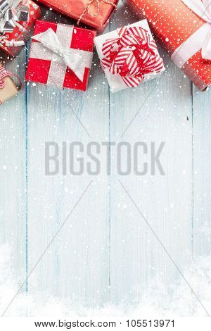 Christmas gift boxes on wooden table with snow. Top view with copy space