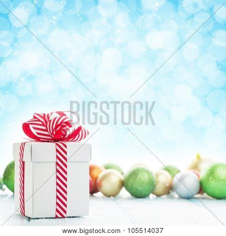 Christmas gift box and colorful baubles decor on wooden table with bokeh background for copy space