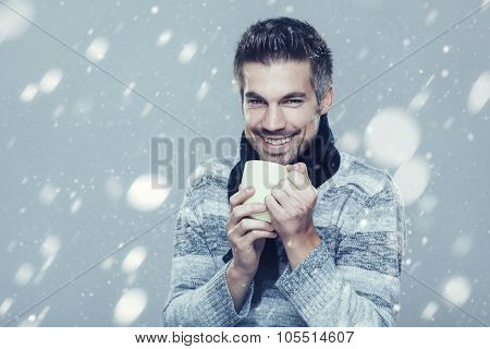 Young Man Is Freezing In The Snow And Holding Cup Of Tea
