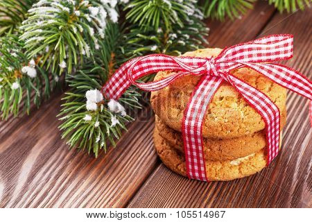 Christmas gingerbread cookies and tree branch on wooden table
