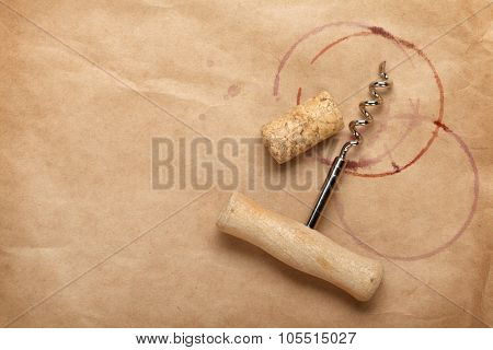 Cork and corkscrew with red wine stains on brown paper background with copy space