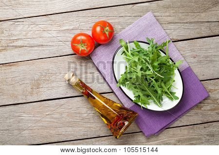 Arugula salad, tomatoes and olive oil bottle over rustic wooden table