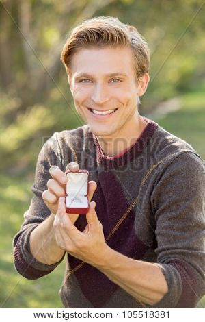 Man kneeling outside proposing with diamond ring