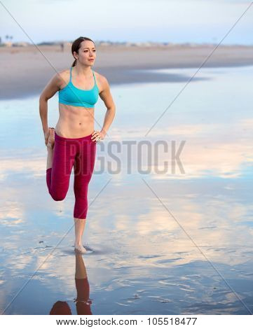 Young woman stretching on the beach at sunset