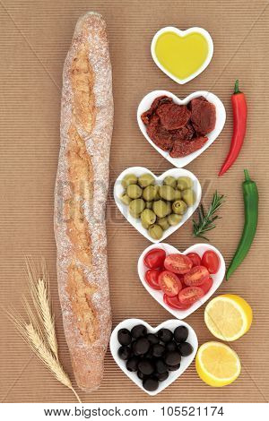 French baguette bread loaf with antipasti selection of fresh and sun dried tomatoes, green and black olives, chilli peppers, olive oil and lemon halves.