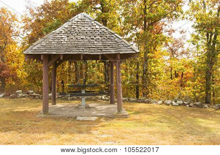 Old fashioned rustic wooden gazebo with a picnic table, against wooded background in fall colors