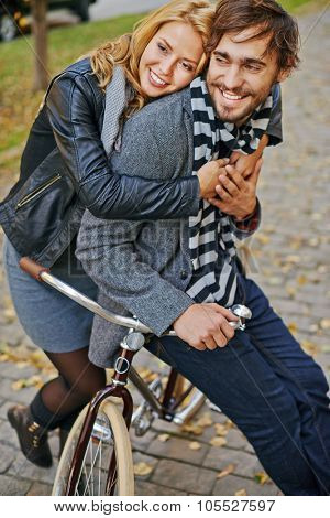 Young amorous girl embracing her boyfriend on bicycle outside