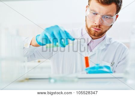 Male chemist mixing up liquid substances in laboratory