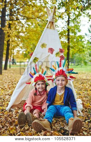 Two friendly kids in Indian headdresses looking at camera while sitting on the ground by wigwam