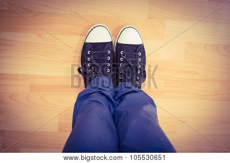 Low section of man wearing canvas shoes standing on hardwood floor