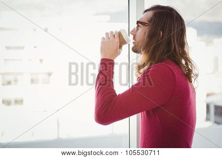 Side view of hipster drinking coffee standing by window in office