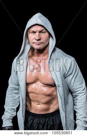 Portrait of confident macho man in hood against black background