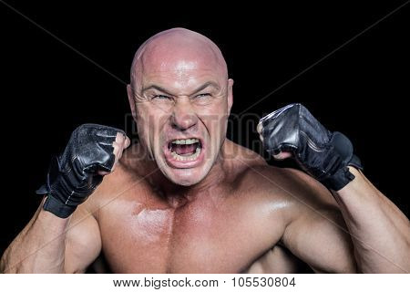 Angry fighter with gloves against black background