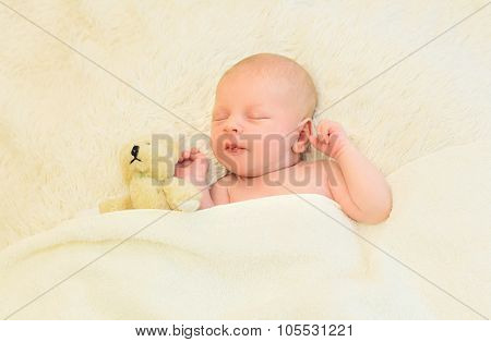 Cute Infant Sleeping Together With Teddy Bear Toy On The Bed At Home