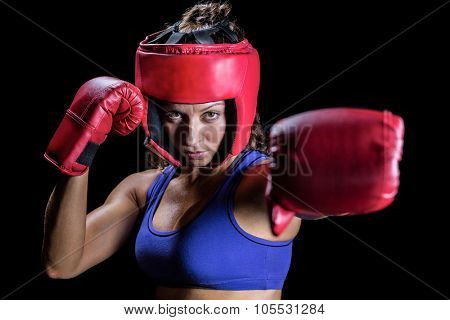 Portrait of female boxer with gloves and headgear against black background