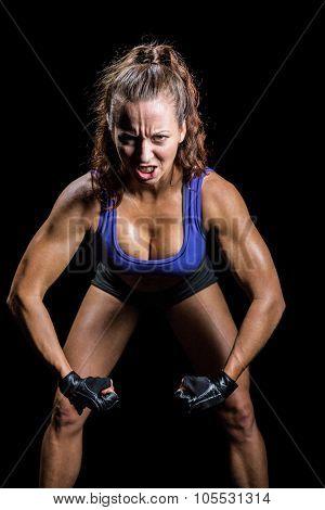 Portrait of aggressive female boxer flexing muscles against black background