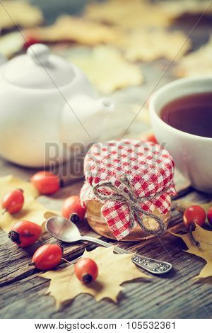 Jar Of Honey, Tea Cup And Teapot On Background. Maple Leaves And Dog Rose Berries On Wooden Table.