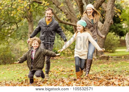 Smiling young family running into leaves on an autumns day