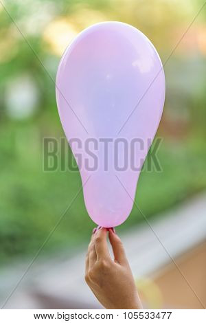 A female hand holding a pink baloon