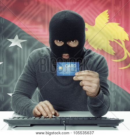 Dark-skinned Hacker With Flag On Background Holding Credit Card - Papua New Guinea