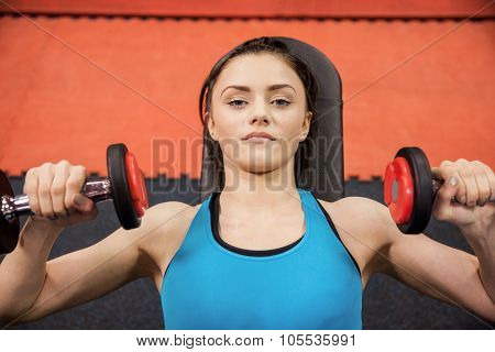 Focused woman lifting dumbbells while lying down at the gym